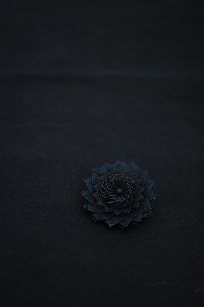 kikka | ブローチ kikka という折り___2016<br> 素材 : 京都 黒谷和紙[黒色染め](和紙職人 ハタノワタル)、樹脂加工<br> 寸法 : 約40mm × 40mm
